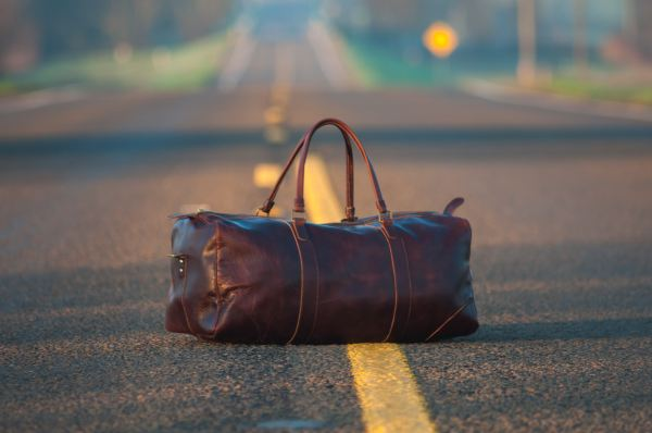 Leather duffel bag on the middle of a highway